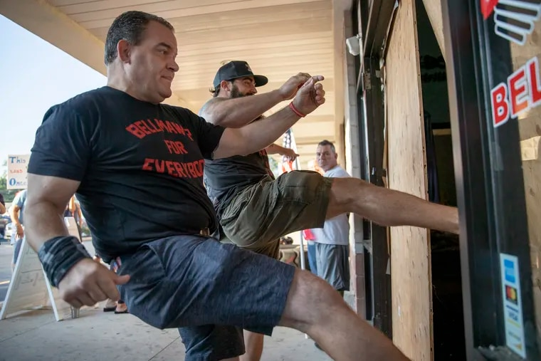 Atilis Gym owners Frank Trumbetti (left) and Ian Smith kick down wooden boards covering the entrance to the facility in Bellmawr on Saturday. Law enforcement officials boarded up the entrance and arrested the owners Monday after they defied a court order to stop operating the gym in violation of state coronavirus restrictions.