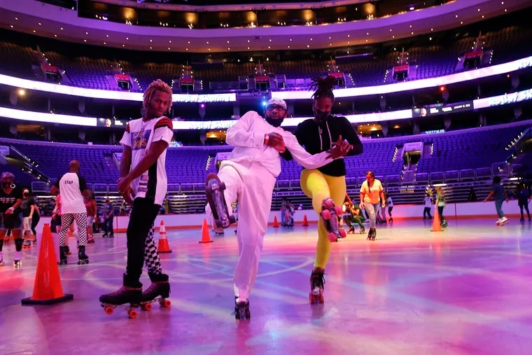 """Roller skater Clyde """"Ice"""" McCoy from South Philadelphia (center) skates with Dominique Dunlap (right) as roller-skating instructor Cameron King moves past them at the roller-skating rink in the Wells Fargo Center."""