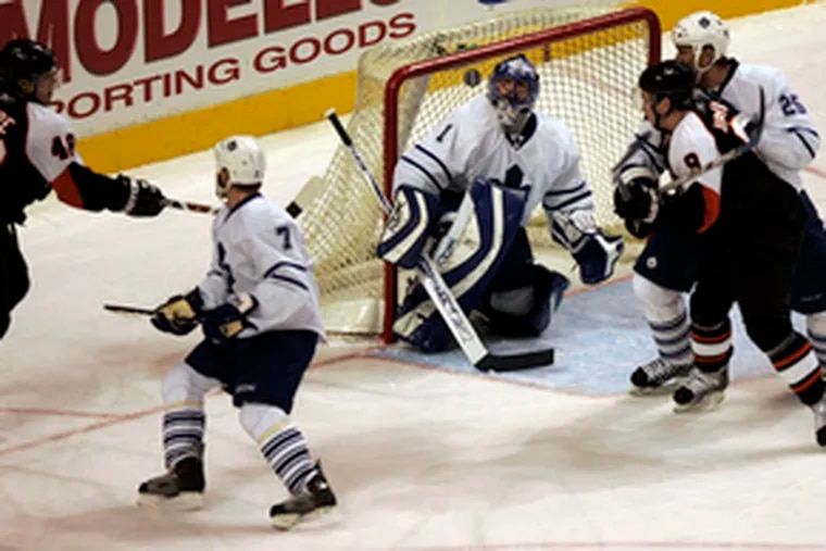 Maple Leafs goalie Andrew Raycroft deflects a shot by Danny Briere (far left) in the first period. Taking part in the action are (from left) Ian White, the Flyers' Scottie Upshall and Hal Gill.