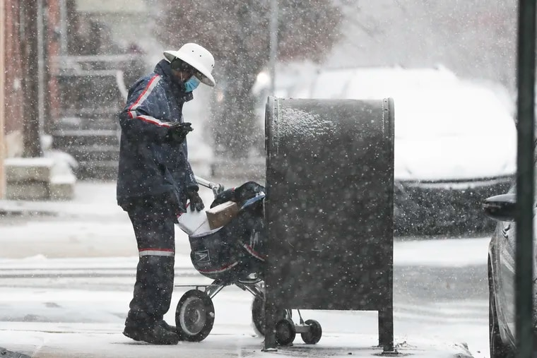 A mail carrier works in a snowstorm by 9th and Reed Streets in South Philadelphia on, Dec. 16.