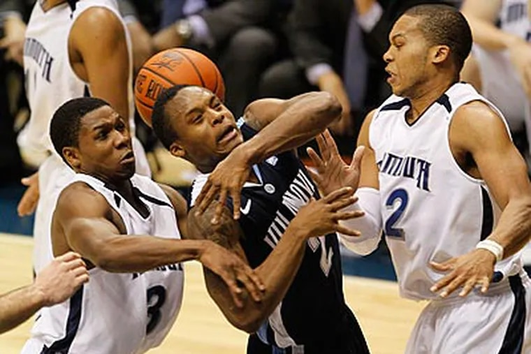 Villanova's Maalik Wayns gets tangled with Monmouth's Will Campbell, left, and Ed Waite in the first half. (AP Photo/Julio Cortez)