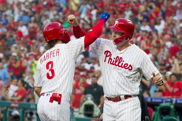 Bryce Harper, left, and Rhys Hoskins of the Phillies celebrate after Harper's 2-run home run off of Cole Hamels of the Cubs in the 1st inning at Citizens Bank Park on Aug. 14, 2019.