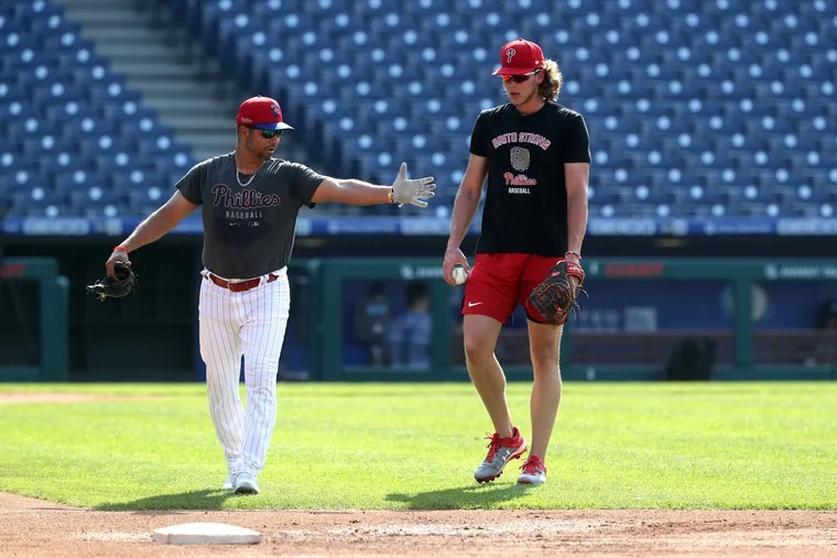 Third baseman Alec Bohm, right, gets a tutorial from Phillies infield coach Juan Castro before a recent game at Citizens Bank Park.