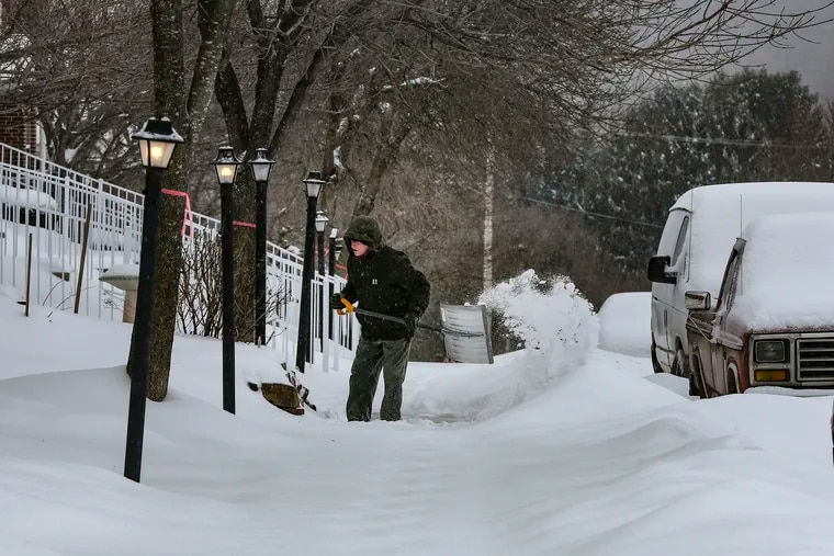 Kevin McCafferty shovels his sidewalk from about 6-8 inches of snow that blankets the Borough of Phoenixville, Thursday, February 19, 2021.