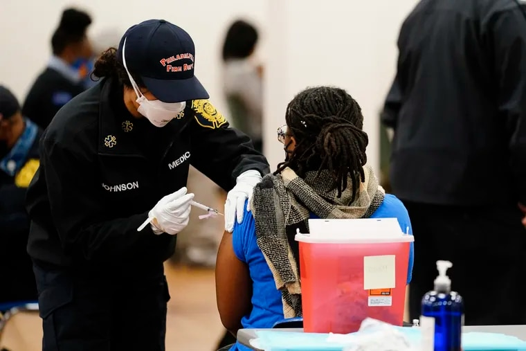 A member of the Philadelphia Fire Department administers a COVID-19 vaccine to a person at a vaccination site in Philadelphia, Monday, March 29, 2021.