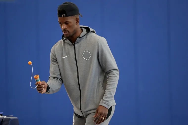 Jimmy Butler works on his eye-hand coordination with a ball and cup toy at the Sixers' practice facility in Camden on Monday.