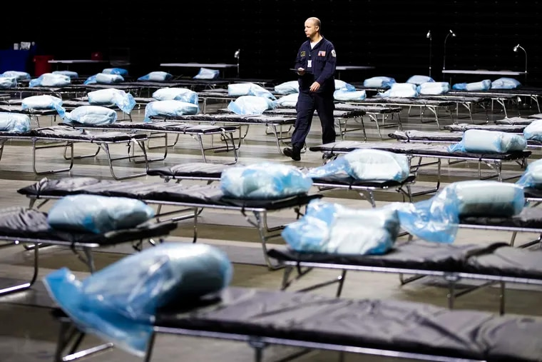 Pennsylvania Task Force 1 member Greg Rogalski walked among the beds of a Federal Medical Station for hospital surge capacity set up at Temple University's Liacouras Center in Philadelphia, Monday, March 30, 2020. So far the center hasn't been reopened as an overflow facility amid the recent surge. (AP Photo/Matt Rourke)