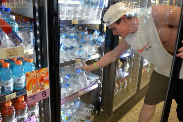 Dan Buzza grabs a few bottles of water from the Wawa on Naamans Creek Road on Friday, July 17, 2015. (Mark C Psoras/For The Inquirer)