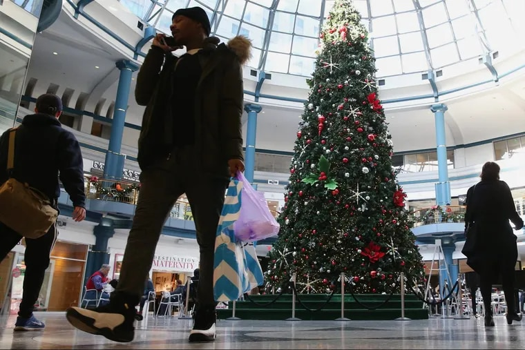 Shoppers walk past the Christmas Tree in the rotunda of the Shops at Liberty Place in Center City this month.