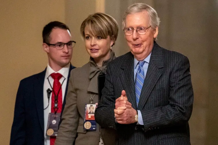 Senate Majority Leader Mitch McConnell (right) walks to meet with Senate Republicans after the Senate voted Friday to not allow witnesses in the impeachment trial of President Donald Trump.