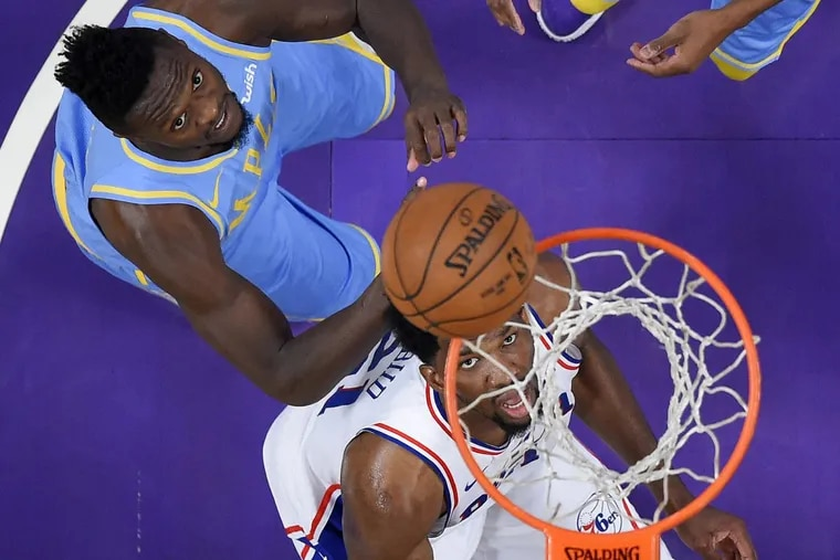 Joel Embiid watches his shot go in the net as he stands in front of Lakers forward Julius Randle during the second half Wednesday night.
