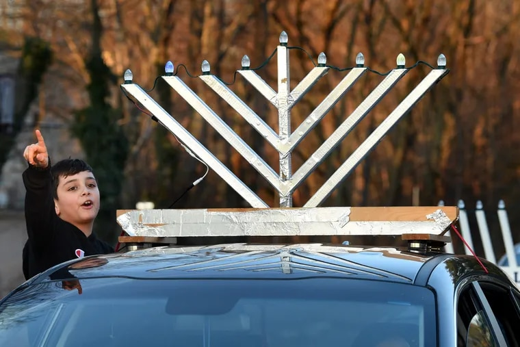 Yonathan Marciano, 9, of Cherry Hill gets ready leave in his family's car, joining the celebration of the first night of the Festival of Lights beginning with a car-top menorah parade by Chabad of Camden & Burlington Counties, to a lighting of the 18 ft. tall outdoor public menorah in the Barclay Farms Shopping Center in Cherry Hill on the first night of Hanukkah Dec. 22, 2019.