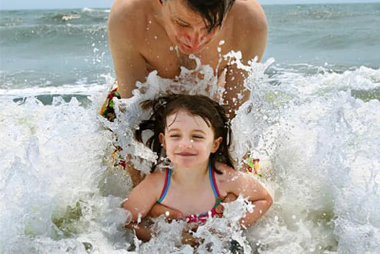 Four-year-old Sophia Dickenson and her father, Rob, play in the surf at Cape May.