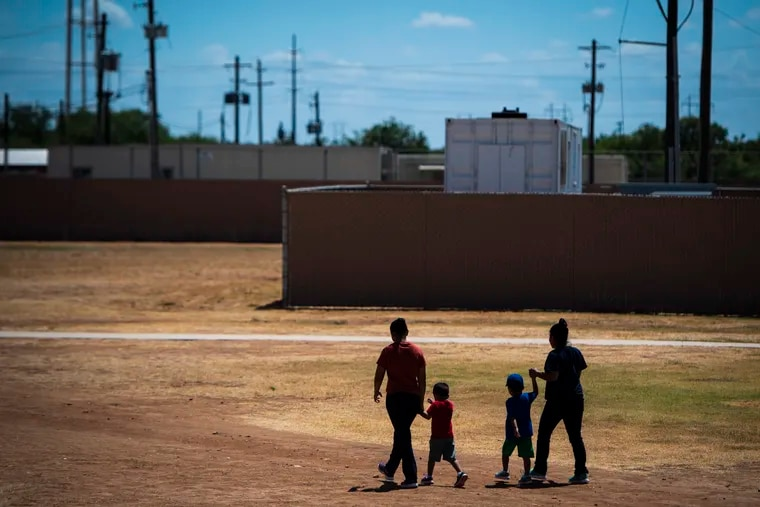 Immigrants walk across a field as U.S. Immigration and Customs Enforcement (ICE) and Enforcement and Removal Operations (ERO) hosts a media tour at the South Texas Family Residential Center, which houses families who are pending disposition of their immigration cases, on Friday in Dilley, Texas.