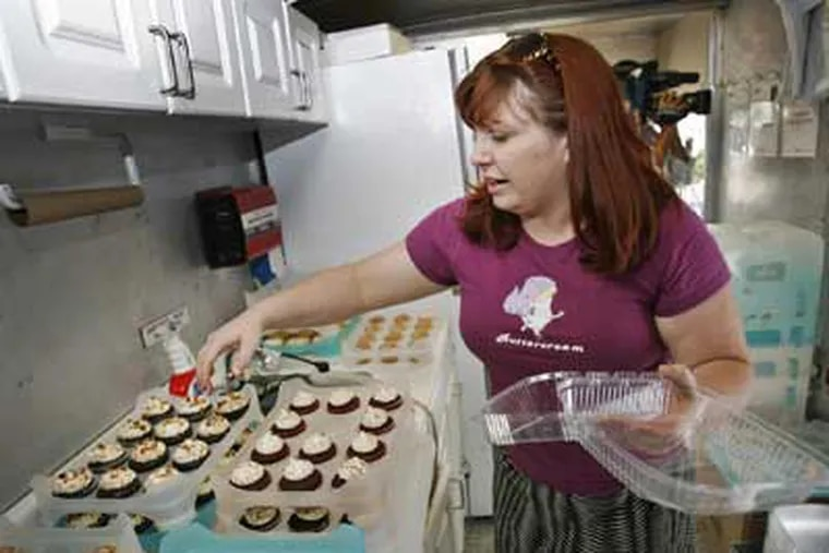 Kate Carrara, the cupcake lady, sells her desserts at JFK Park in Center City Philadelphia today. She's pictured inside her truck gathering an order for a customer. (Alejandro A. Alvarez / Staff Photographer)