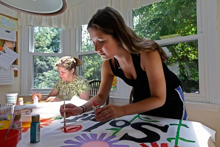 """Devon Braunstein (right) paints a red flower banner that will be carried during the """"Clean Energy March"""" from Philadelphia City Hall to Independence Mall. Her group is part of the """"Solutions Brigade"""" during the march."""