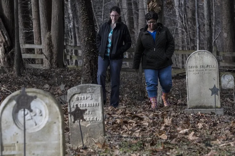 Crystal Crampton, right, and Abbie Kessler, preservation director at the Land Conservancy of Southern Chester County, walk through the Historic Bucktoe Cemetery in Kennett, Pa.  Both women are part of a team working to preserve the African American cemetery that dates back to the early 1800s.