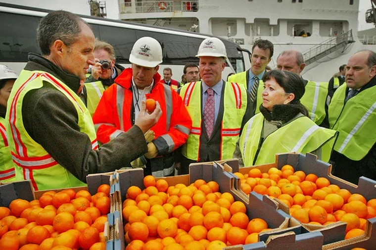 """FRANCISCO CAMPS, president of the Spanish province of Valencia, visits Holt Logistics Corp., of Gloucester City, N.J. yesterday. Valencia is the largest exporter of clementines, known as the """"Christmas fruit,"""" in the world. Hundreds of boxes of clementines will be donated to Philabundance, the Delaware Valley's largest hunger-relief organization. At right is Martha Buccino, senior vice president of Philabundance."""