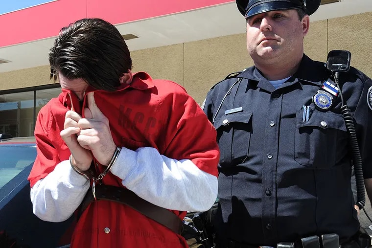 Neil K. Scott, 25, Haverford, covers his face after he was arraigned in Montgomery County Magisterial District Court and charged with allegedly the leader of a drug distribution ring April 21, 2014.  The ring sold drugs to local high schools and colleges.  ( CLEM MURRAY / Staff Photographer )