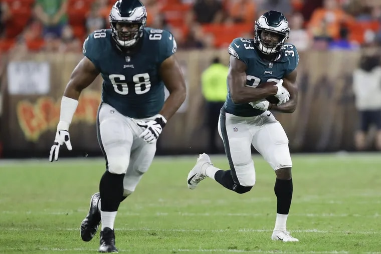 Eagles running back Josh Adams runs with the football behind offensive tackle Jordan Mailata against the Cleveland Browns during a preseason game at FirstEnergy Stadium in Cleveland on Thursday, August 23, 2018. YONG KIM / Staff Photographer