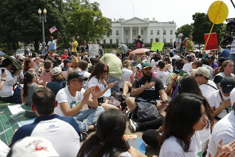 Demonstrators sit on the ground along Pennsylvania Ave. in front of the White House in Washington in April 2017. The Trump's administration's National Park Service is exploring higher fees and much stricter limits on future D.C. protests.