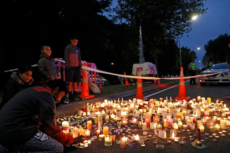 A mourner lights a candle during a vigil to commemorate victims of Friday's shooting, outside the Al Noor mosque in Christchurch, New Zealand, Monday, March 18, 2019. Three days after Friday's attack, New Zealand's deadliest shooting in modern history, relatives were anxiously waiting for word on when they can bury their loved ones.