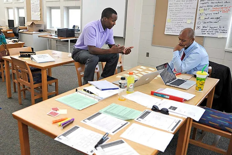 File photo: Tim Jenkins (left), MetEast High School principal, and Darrell Staton, lead educator, participate in a summer institute focused on developing lesson plans, coaching teachers.