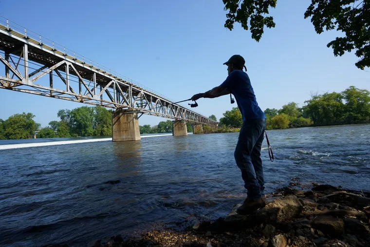 Kevin Rodenbaugh, 20, of King of Prussia, who recently caught a 45-inch Muskie in the Schuylkill, shown here fishing off the banks of the Schuykill River, near Bridgeton, PA.