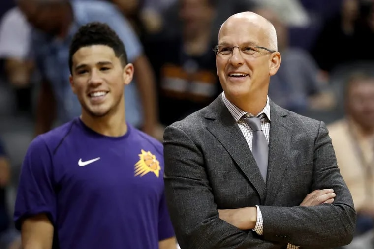 Suns coach Jay Triano, next to guard Devin Booker, smiles during a game in October.