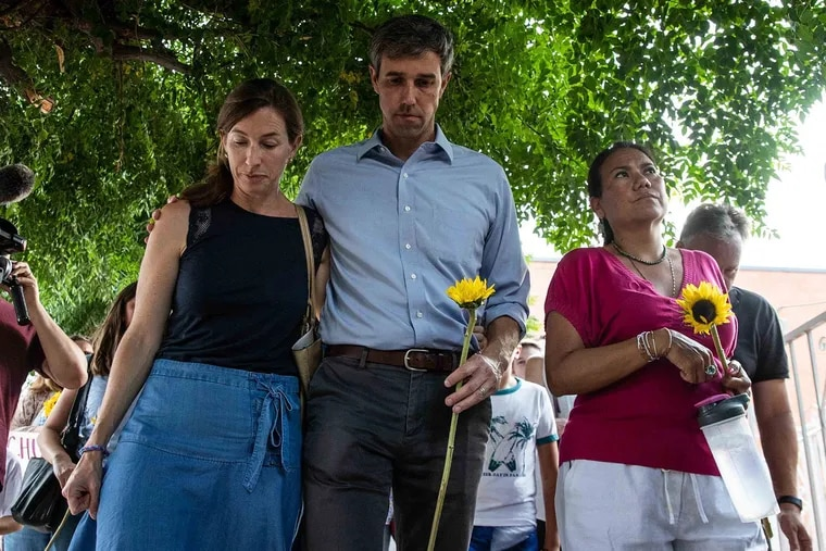 Democratic presidential candidate Beto O'Rourke walks next to his wife Amy Hoover Sanders and US Rep. Veronica Escobar during a silent march holding sunflowers in honor to the victims of a mass shooting occurred in Walmart on Satuday morning in El Paso on Sunday, August 4, 2019.