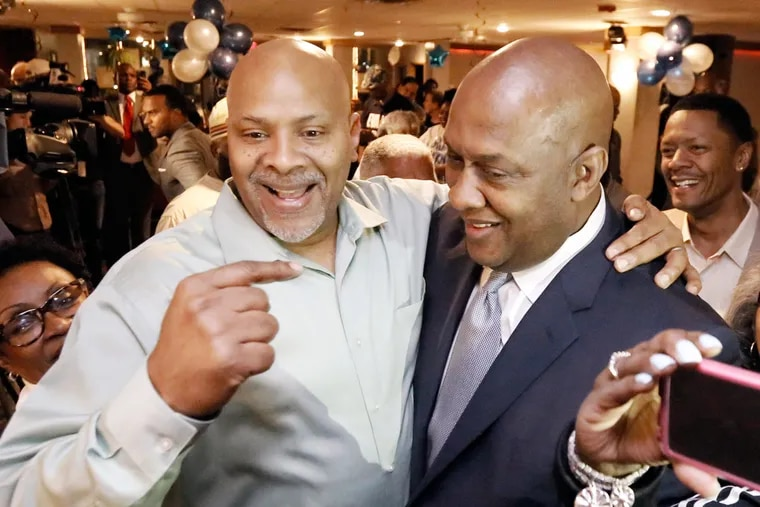 Dwight Evans (right), Democratic nominee for Congress, is greeted by his brother, Gary, at Temptations banquet hall.