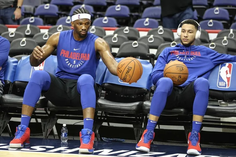 Sixers' Joel Embiid and Ben Simmons watch warmups before their game against the Wizards on Wednesday night.