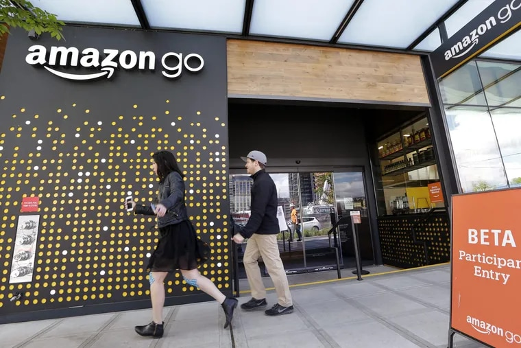 People walk past an Amazon Go store in Seattle on Monday, Jan. 22, 2018.
