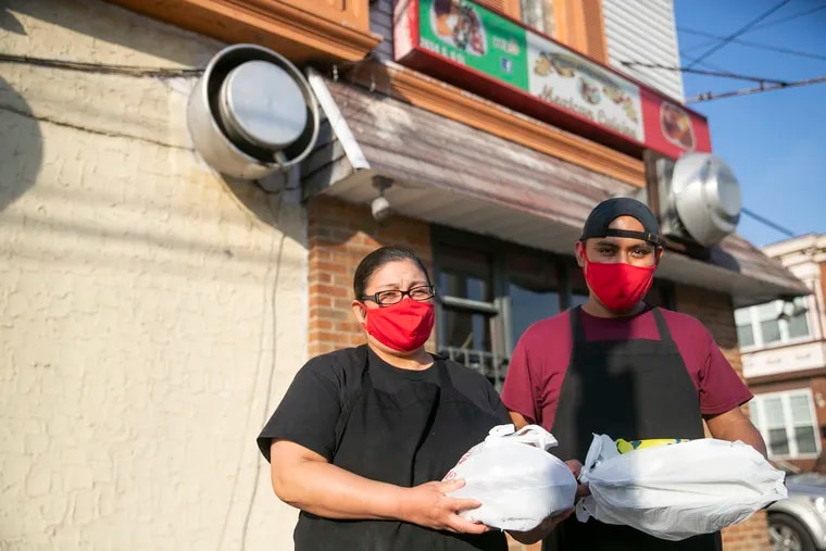 Aurora Hernandez, left, chef/owner, and Adolfo Florencio, also a chef at San Miguelito, pose for a portrait in front of the restaurant at the corner of Sixth and Oregon Ave. in South Philadelphia.