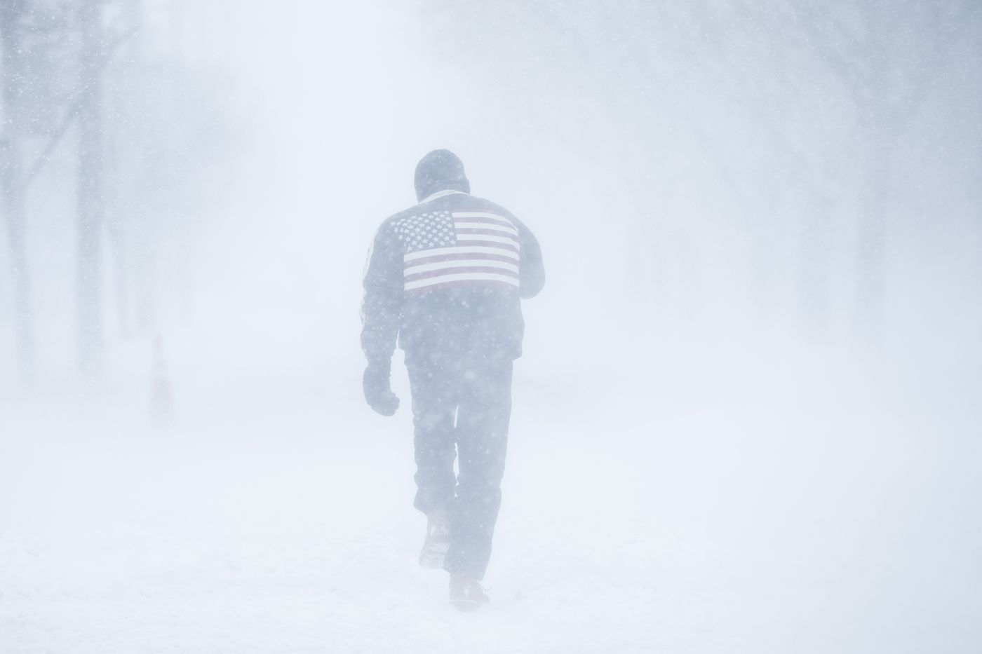 A man pushes his way through driving winds during a winter snowstorm in  Atlantic City on