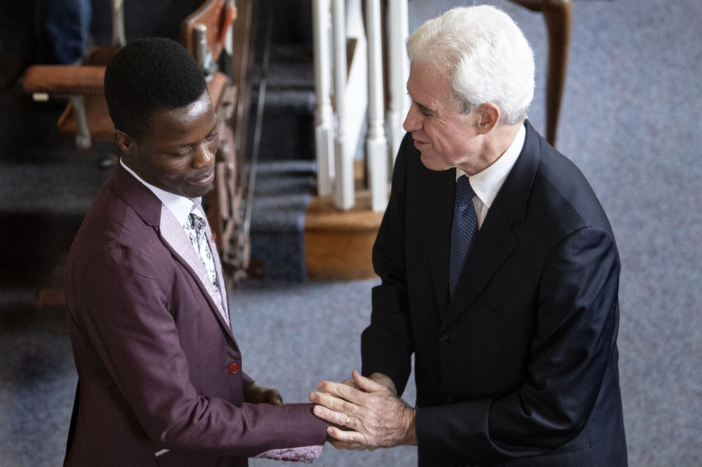 Pastor Cliff Jones, right, greets Marcel Njighe, who's originally from Cameroon, at St. Paul's Presbyterian Church in Laurel Springs. The congregation prays for Cameroon, which some observers describe as on the verge of civil war. Jones said the people in his flock also want to learn more about the situation, and to do more to help.