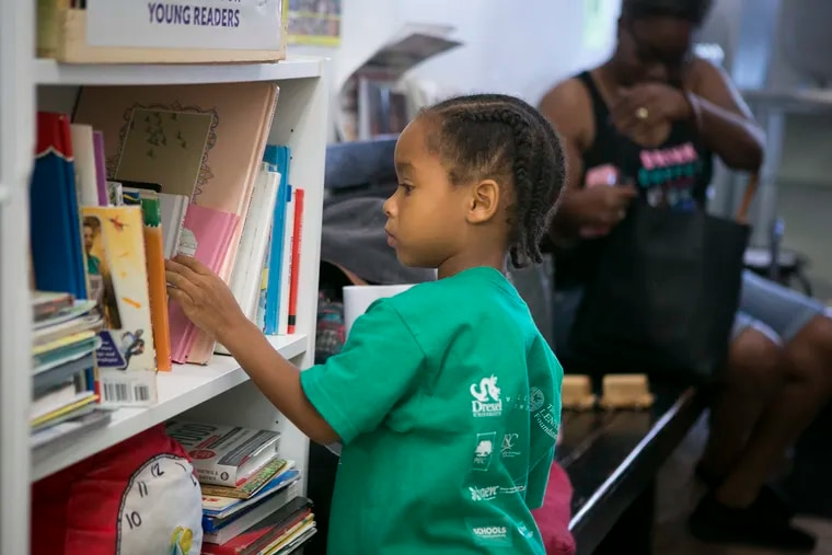 Christopher Parnell, 4, chooses a book at Leroy's Barbershop on Lancaster Avenue in West Philadelphia. Placing free books in local businesses is one grassroots strategy employed by Read by 4th, the multimillion-dollar citywide campaign to improve citywide literacy rates.