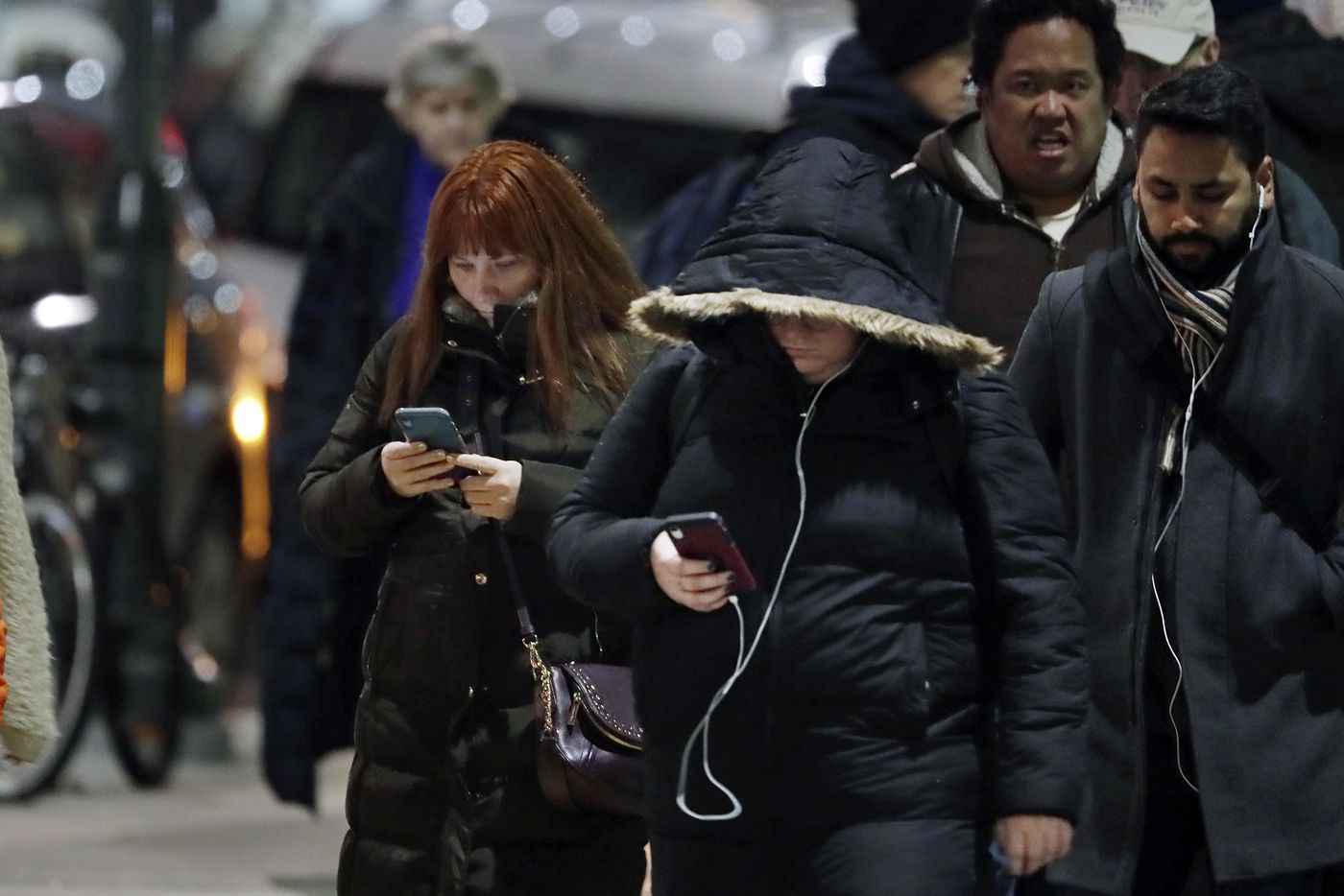 People engaged with their cell phones wait to cross Market Street during the evening rush hour.