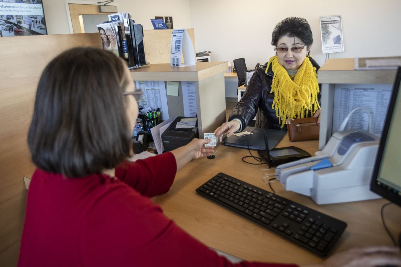 Alla Fisun, right, who has been a customer of the Ukrainian Selfreliance Credit Union for 27 years, works with head teller Tatyana Mariyanich, left, in the customer area of the Feasterville location.