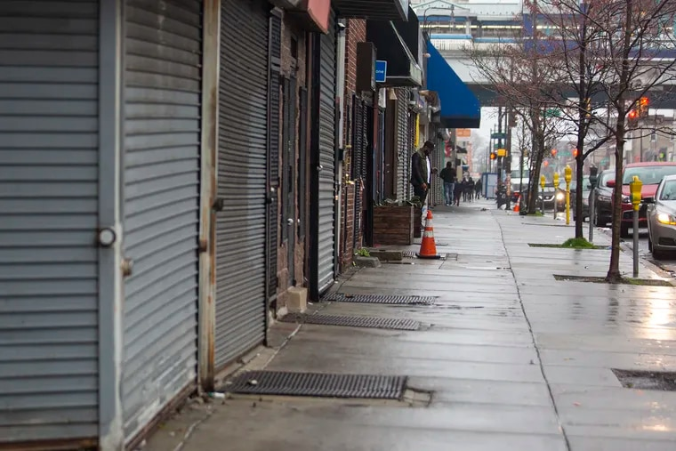 A man standing on the sidewalk on 52nd Street is surrounded by local businesses that are closed last month.