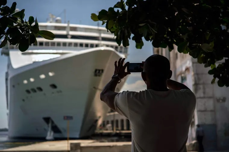 A man takes a photo of a cruise ship in Havana harbor in June.