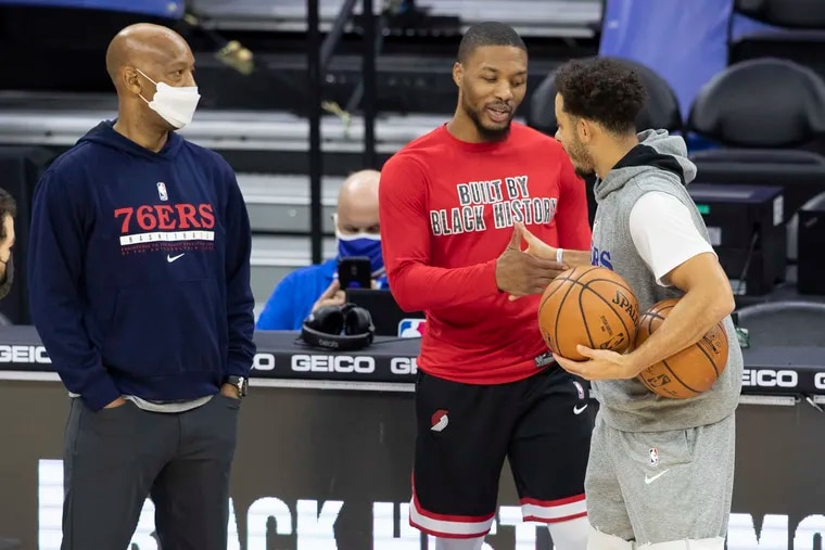 Portland assistant coach Sam Cassell (left) and the Sixers' Seth Curry (right) talk with the Trail Blazers' Damian Lillard before a game at Wells Fargo Center last season.