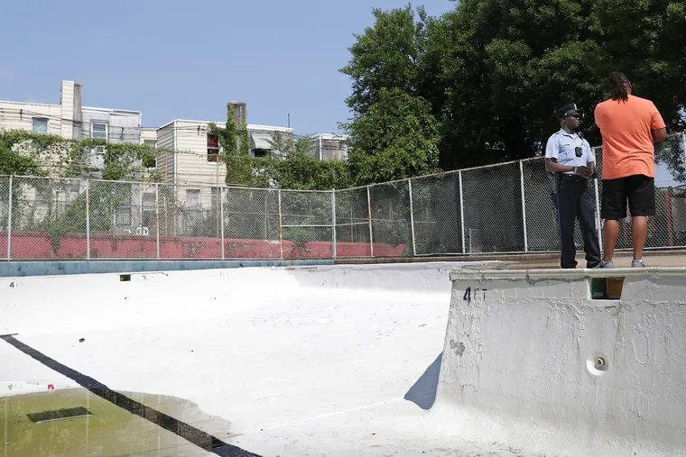 Officer Wilfrid Etienne, left, talks with Donnell Martin, right, of the Belfield Recreation Center, as they stand next to an empty pool. The pool was drained Friday after a shooting between street crews.