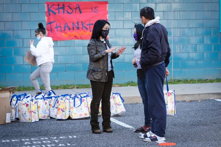 Councilperson Helen Gym greets community members as Kensington Health Sciences Academy hosts Friendsgiving, a Thanksgiving event to give away turkeys and side dishes, in Philadelphia, Friday, November 20, 2020.