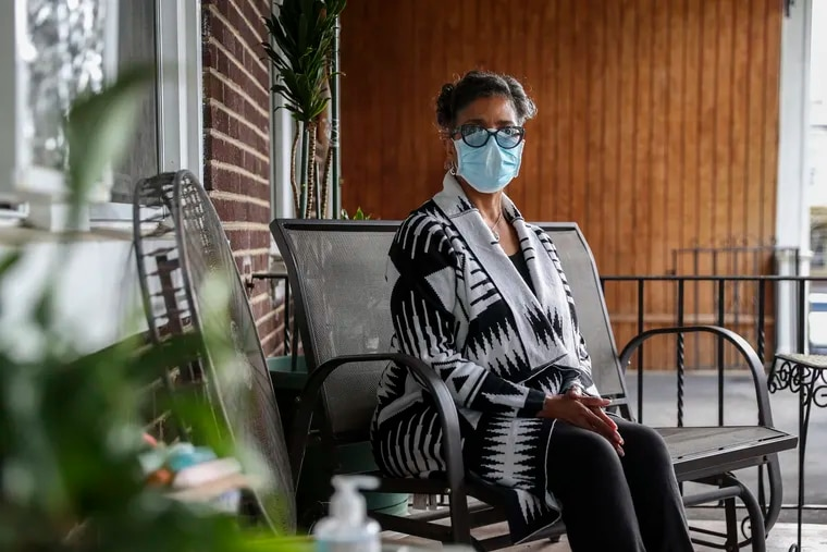 Sherrelle Pritchette on her front porch in Philadelphia. Prichette's mother and sister both died this spring after contracting the coronavirus.