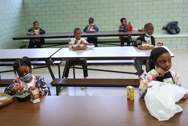Students sit socially distant as they eat lunch in the cafeteria at William Dick Elementary in North Philadelphia in May.