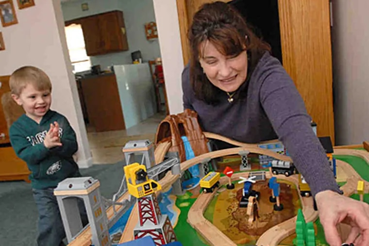 """""""Without a job,"""" Donna Oxford says, """"you can never be relaxed or secure."""" Here, she plays with grandson Michael in their Coatesville home. (April Saul/Staff)"""