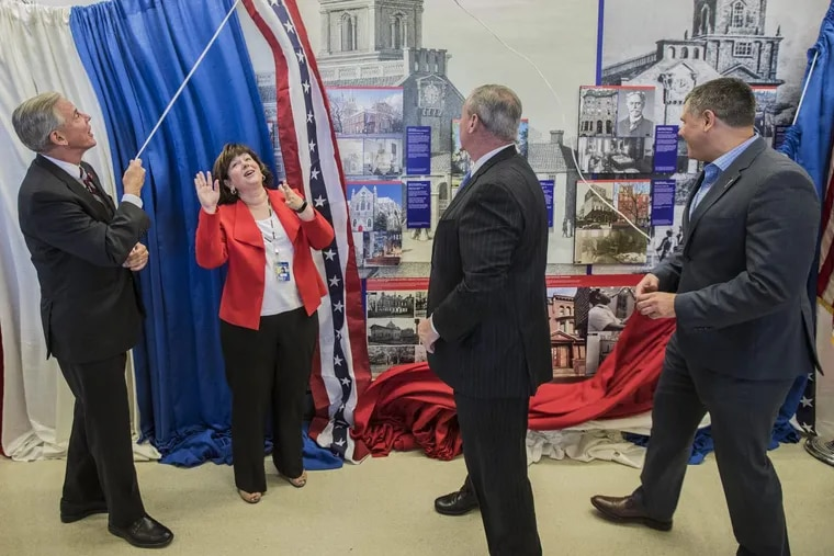 Chellie Cameron, Airport CEO, second from left, reacts as the bunting that was hiding the new art exhibit at the airport was pulled down by John Smith, left, Board Chair of Global Philadelphia Association, Mayor Jim Kenney, and Jeff Guaracini, Director of Wawa Welcome America, on Wednesday, June 28, 2017.