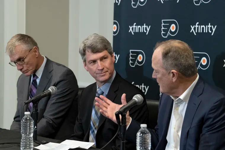 Flyers GM Chuck Fletcher (center) and club chairman Dave Scott (right) are trying to improve the team's future schedules. In this fie photo, former club president Paul Holmgren is to the left.