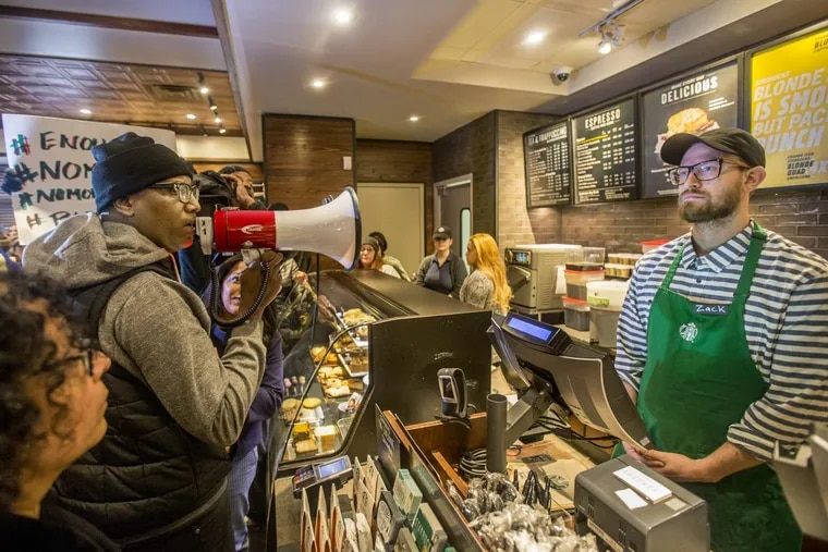 Black Lives Matter activist Asa Khalif, left, stands inside the Starbucks at 18th and Spruce, and over a bullhorn, demands the firing of the manager that called police, resulting in two black men being arrested.